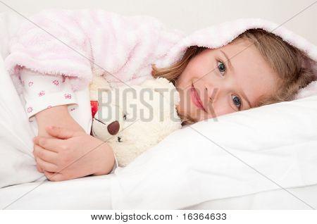 Cute girl in bed hugging no-name teddy bear