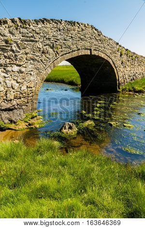 Eighteenth Century stone hump back bridge with water channel the river Ffraw and blue sky. Aberffraw Anglesey Wales United Kingdom Europe