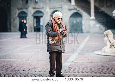 BERGAMO, ITALY - DECEMBER 2016: Senior man is using mobile phone at street of Bergamo town, Italy