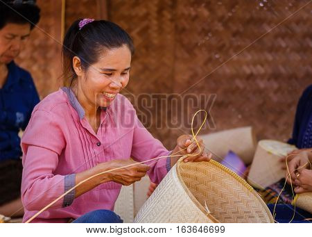 BANGKOK, THAILAND - JANUARY 14 2016: Unidentified female makes Thai bamboo basket  in the celebration of Thai Traditional Culture Festival at Lumpini Park