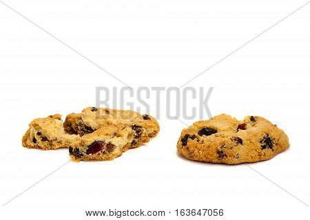 Two cookies with raisins broken into pieces isolated on white background.