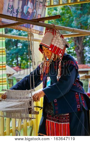 BANGKOK, THAILAND - JANUARY 14 2016: Unidentified female hill tribe displays cloth weaving at Thai traditional culture festival