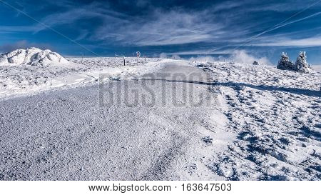 winter hiking trail with snow, isolated shrub and blue sky with clouds near Geiereck hill on Stuhleck mountain ridge in Fischbacher Alpen mountains in Styria