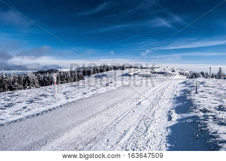 winter hiking trail with snow and blue sky with few clouds in Fischbacher Alpen mountains in Styria