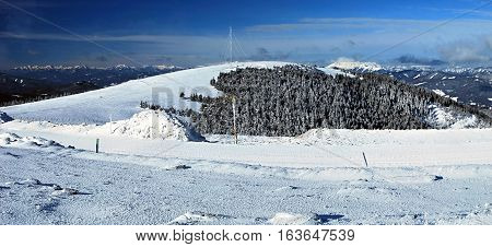 Admunsenhohe hill with higher peaks of austrian mountains on the background from Pretulalpe hill on Stuhleck mountain ridge in Fischbacher Alpen mountains in Styria during nice winter day with snow and blue sky with only few clouds