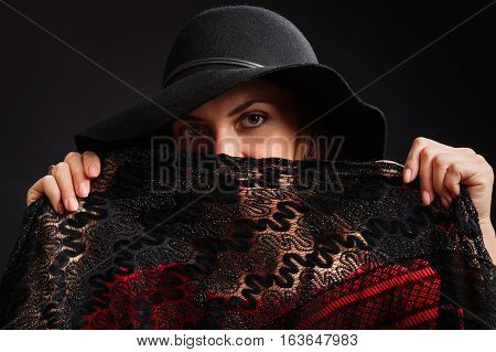 The young beautiful woman in a black wide-brimmed hat and an elegant dress of scarlet color closes the lower part of the person a black openwork shawl.