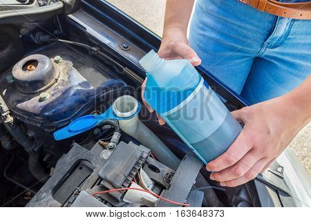 Woman filling car reservoir with windshield wiper fluid