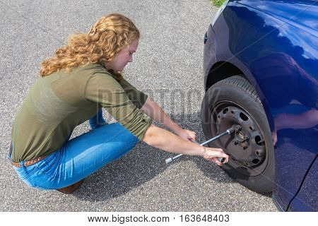 Caucasian teenage girl changing car wheel on street