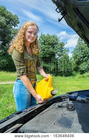 Young dutch teenage girl filling car motor with oil in yellow jerrycan