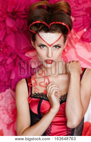 Beautiful sexy lady seductively looking at camera. Portrait of attractive lady in red lingerie, with valentines day makeup, pink background. Love, sex, seduction, temptation concept
