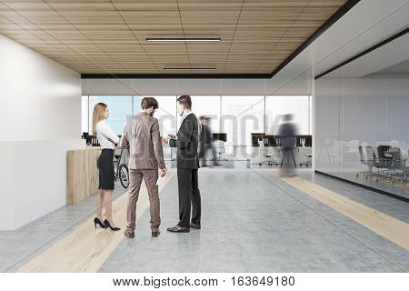 People talking in an office near a reception counter. A man is heading to the work area. Conference room is seen in the left part of the picture. 3d rendering. Mock up