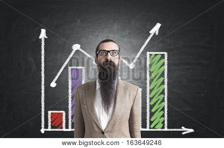 Close up of a baffled businessman with a long beard standing in a beige suit near a blackboard with a red and green graph. Concept of success
