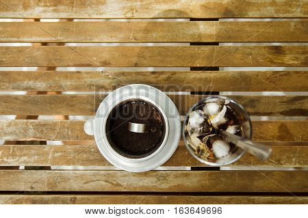 Glass of Ice coffee & Vietnamese traditional coffee filter on wooden table in nature light