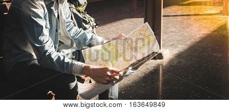 Traveler Sitting And Looking In Map For Waiting Train At Train Station. Travel Concept By Train With