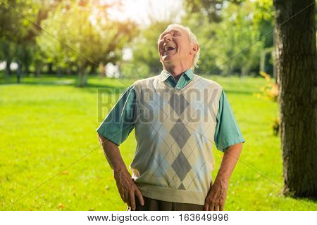 Elderly man is laughing. Person on park background. Share good mood with others. Humor and jokes.