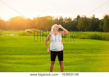 Woman drinking water from bottle. Lady standing on green grass. Training is finished. Tiredness and thirst.