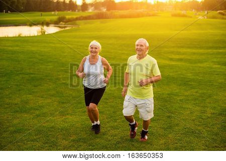 Elderly couple jogging. Smiling people on grass background. Former professional athletes. Health of cardiovascular system.