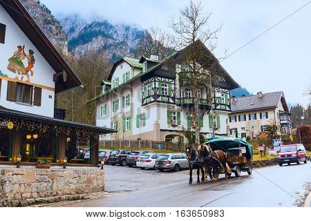 Fussen, Germany - December 27, 2016: Beautiful painted traditional bavarian houses near Neuschwanstein in german alps in Bavaria and fiaker with horses