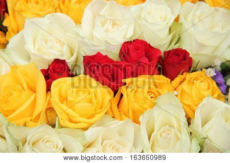Yellow red and white roses in a wedding centerpiece