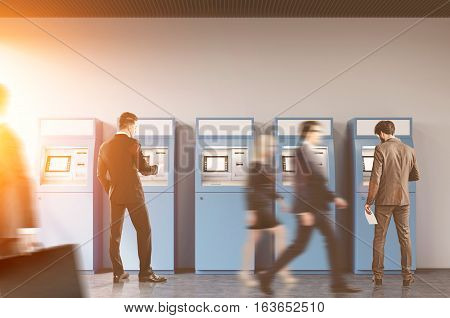 Hallway of an office or a bank. People are rushing by. Two businessmen are standing near ATM machines. There is a cityscape on the foreground. Toned image.