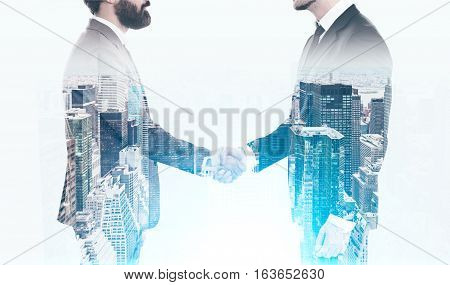 Close up of two businessmen shaking hands and wearing suits. There is a large city view in the foreground. Concept of business meeting. Toned image. Double exposure