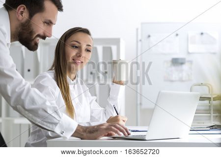 Portrait of a man and a woman in a white office. They are working at one laptop. He is pressing a key. She is looking at the screen and holding a cup of coffee