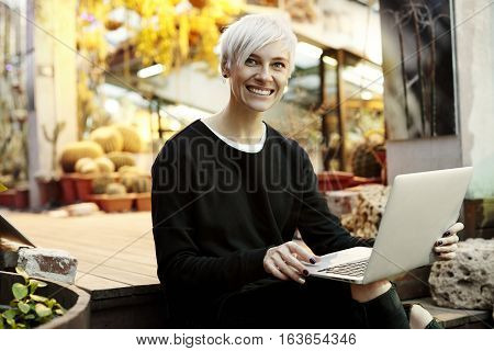 Young hipster woman with blonde short hair smiling and working on laptop sitting on stairs. Indoor botanical garden interior