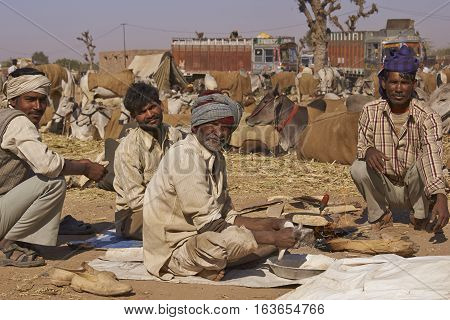 NAGAUR, RAJASTHAN, INDIA - FEBRUARY 15, 2008: Group of men prepare the first meal of the day after a night in the open at the annual livestock fair in Nagaur, India.