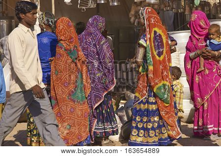 NAGAUR, RAJASTHAN, INDIA - FEBRUARY 16, 2008: Group of women in brightly coloured clothing shopping amongst the many temporary stalls at the annual livestock fair in Nagaur, India.