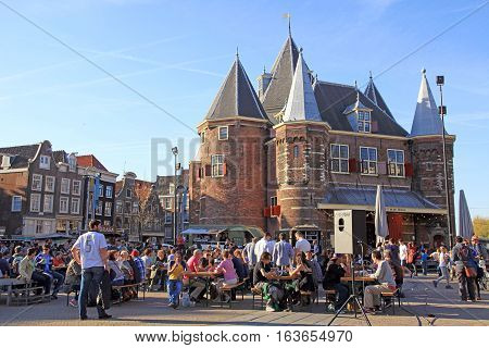 AMSTERDAM, NETHERLANDS - MAY 5, 2016: People in outdoor cafe on Nieuwmarkt (New Market or Newmarket) square in the center of Amsterdam, Netherlands. The Waag (