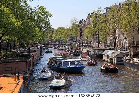 AMSTERDAM, THE NEDERLANDS - MAY 8, 2016: Amsterdam canals full of boats and people in Amsterdam, The Netherlands