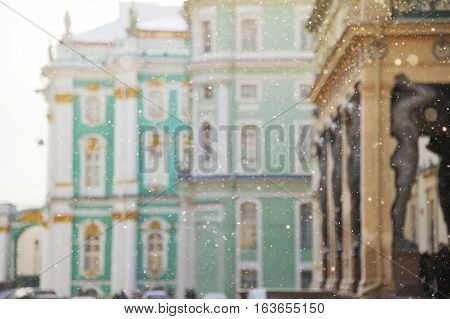 Cold winter in Saint-Petersburg. In the background through the storm with blurred focus see the Hermitage and the granite sculpture of the Atlanteans.