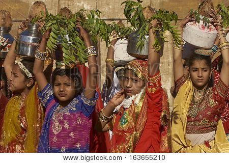 JAISALMER, INDIA - FEBRUARY 19, 2008: Group of young Indian woman in brightly colored clothing carrying silver pots on their heads as part of the Desert Festival in Jaisalmer, Rajasthan, India.