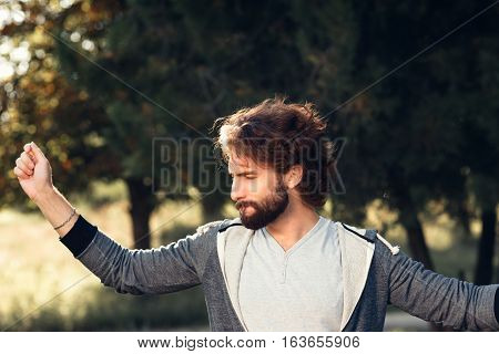 Young satisfied man in forest portrait. Happy pleased guy enjoy being outdoor, free space on green trees background. Pleasure, happiness, joy, life love, unity with nature concept