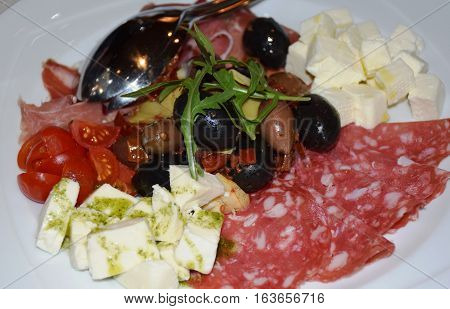 Pieces of wurst salami cuts with vegetables, tomatoes cherry, olives, cottege cheese and rocket salad on a plate