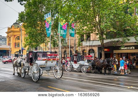 Melbourne Australia - December 27 2016: Horse drawn carriages with tourists departing from Flinders Street station opposite Federation Square.
