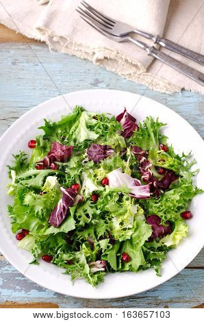 Green salad with spinach, frisee, arugula, radicchio and pomegranate seeds on blue wooden background, vertical
