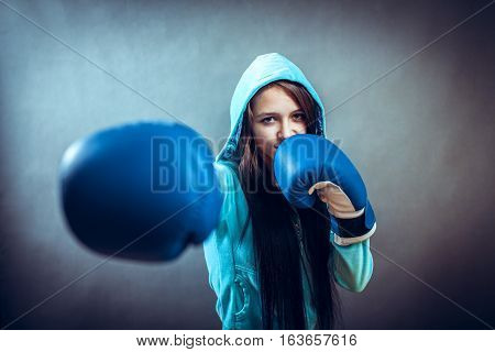 Young woman training punch boxing gloves, studio