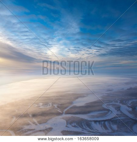 The Aerial view the river on snow-covered forest plain in time of cold winter day. Network of seismic tracks of geophysical exploration in Western Siberia, top view