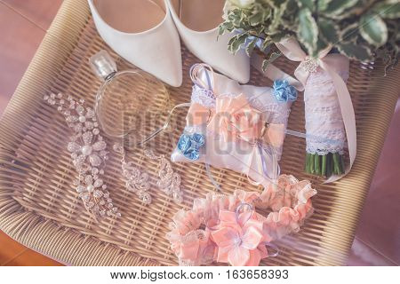 Wedding accessories: perfume bottle and a garter on table