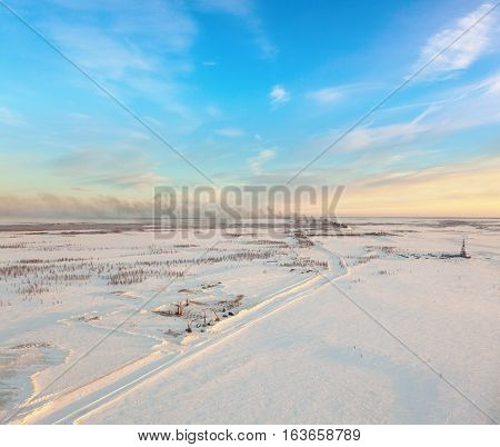 Aerial view of oil rig at an oil field in Western Siberia in the winter day. Gas-jet for gas flaring is located near the rig.