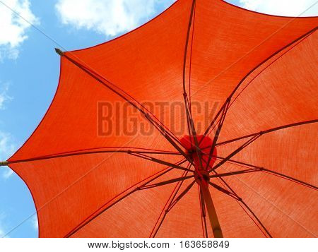 One vibrant orange colored sunshade against vivid blue sky and white cloud