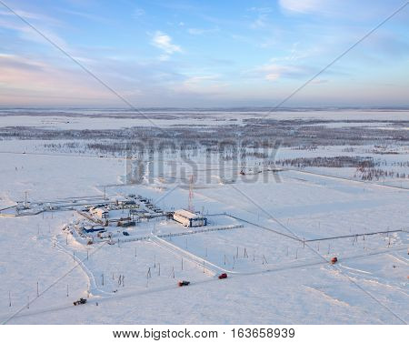Aerial view of oil rig at an oil field in Western Siberia in the winter day. This is a station the primary processing of gas condensate. Special transports move to oil field on the road. There is a connected tower, through which passed all the parameters
