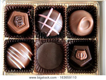 Box of six decorated chocolates, one of them missing