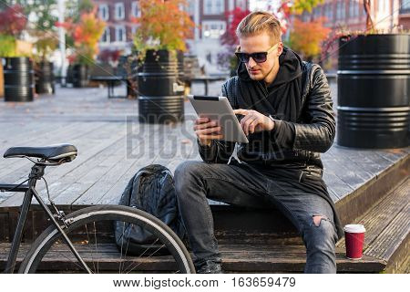 Man sitting and using tablet min city