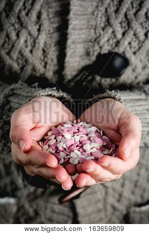 Female hands holding sweet candy hearts.Vertical imagen