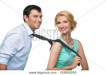 Beautiful blond young woman in mint dress is pulling man in blue shirt for his black tie. Happy expression. Isolated on white background. Copy space.