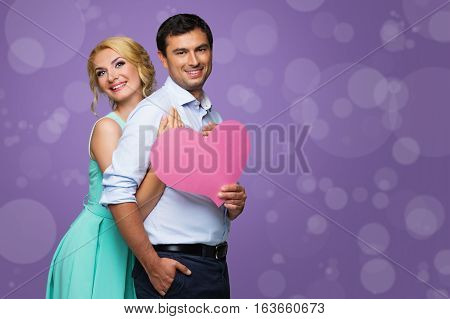 Beautiful young couple holding big pink heart. Blond woman in mint dress and handsome man in shirt and trousers standing on purple background. Valentine's day concept. People in love. Copy space.