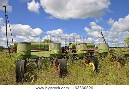 An old discarded four row corn planter  is left in the weeds and grass