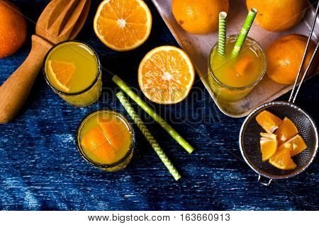 Orange drink in a glass on a background of mandarins. Selective focus.